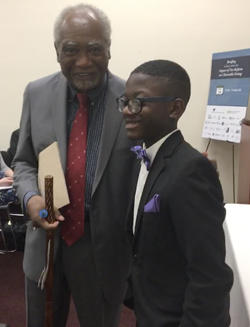 Rep. Danny Davis speaks with Joshua Grandy, a musician from Baltimore Symphony Orchestra's OrchKids program, at a 2017 charitable giving briefing in Washington, D.C.