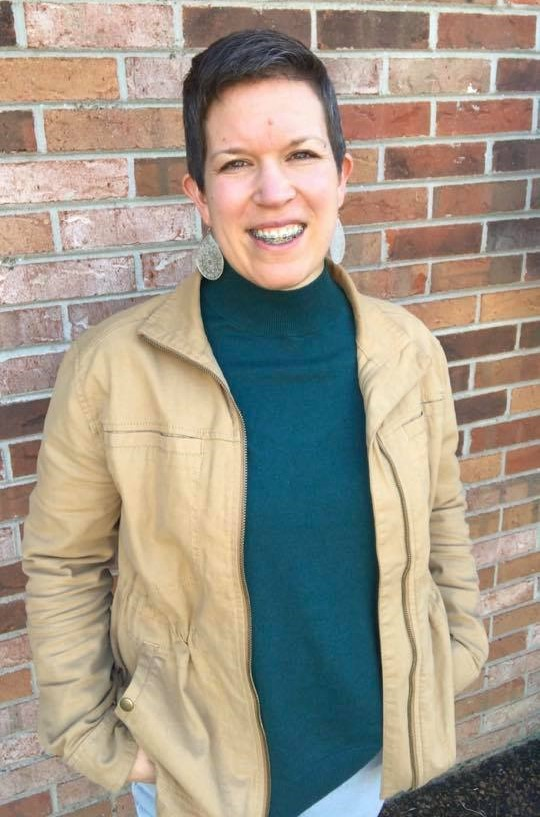 Photo of Sonja Thoms standing in front of a brick wall